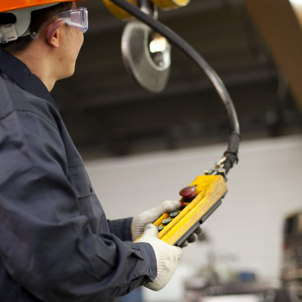 Worker holding crane hook button working in factory with safety workwear